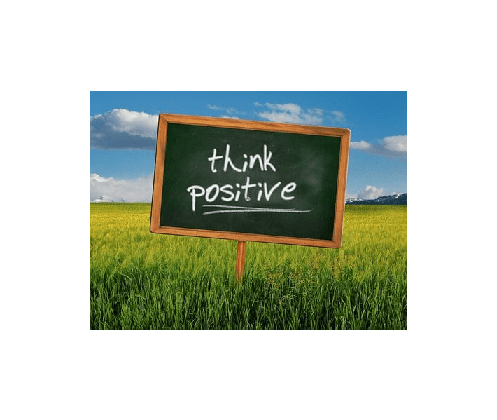 """words """"think positive"""" on chalkboard sign in grassy field"""