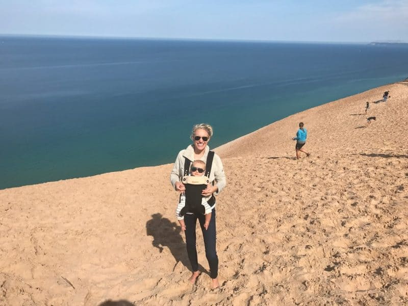 woman and son sand dunes | Living in Michigan by popular Michigan lifestyle blog, The House of Navy: image of a mom holding her baby in a baby carrier at Sleeping Bear Dunes, MI.