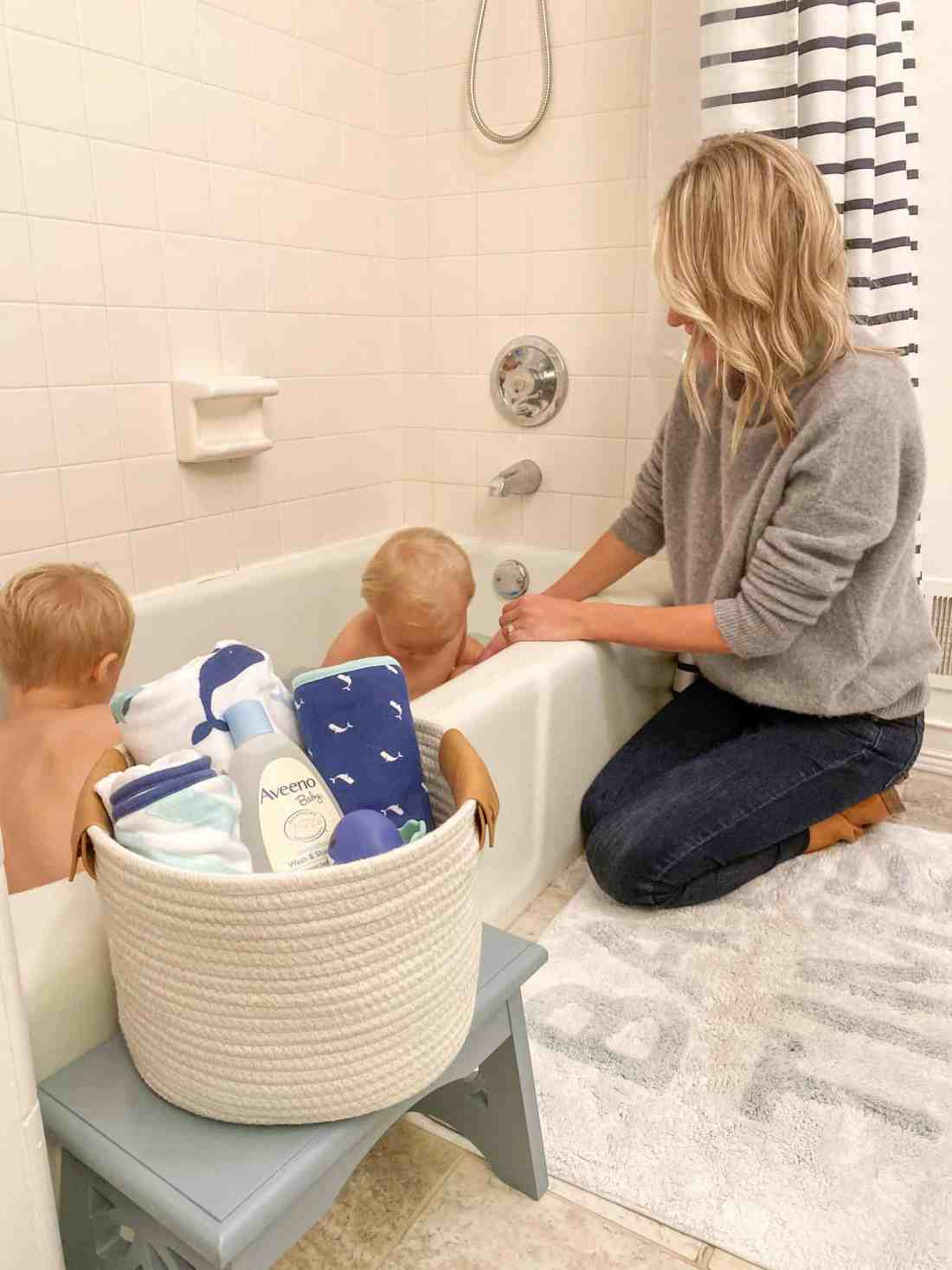 Bath and Bedtime Routine with Aveeno® Baby featured by top Michigan lifestyle blogger, The House of Navy: mom with sons at bathtime | Aveeno Baby by popular Michigan motherhood blog, House of Navy: image of a two young boys sitting in a bathtub next to a white woven basket filled with a blue and white stripe hooded towel, whale print wash cloth, and Aveeno Baby wash and shampoo.