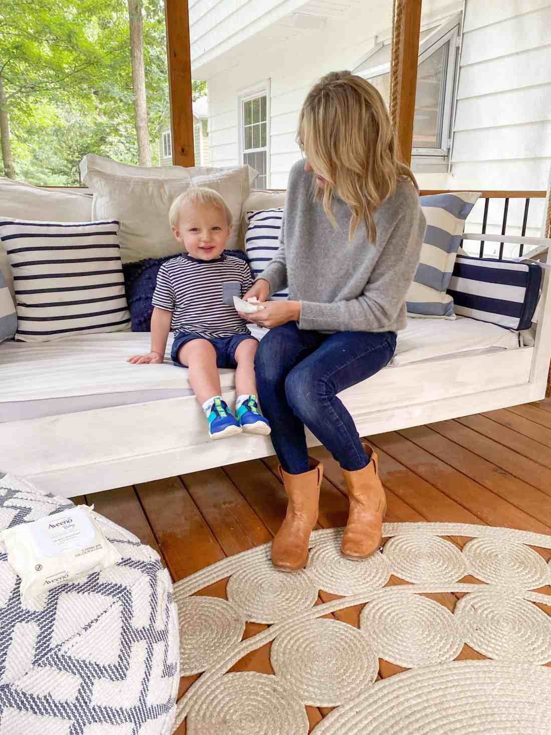 Bath and Bedtime Routine with Aveeno® Baby featured by top Michigan lifestyle blogger, The House of Navy: mom and son cleaning hands | Aveeno Baby by popular Michigan motherhood blog, House of Navy: image of a mom and her young son sitting outside on a porch swing as the mom wipes her sons hands off with Aveeno Baby wipes.