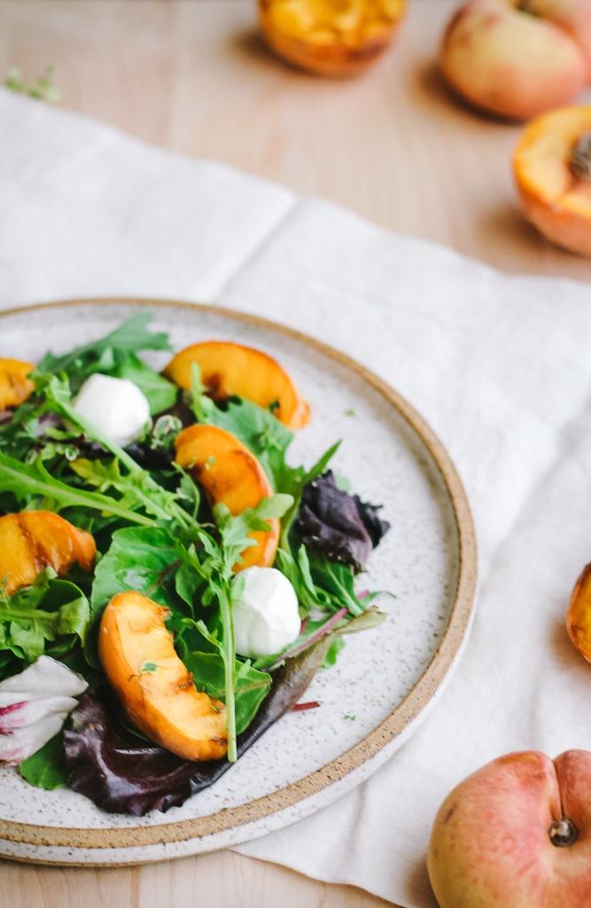A peach salad on a plate over a napkin.