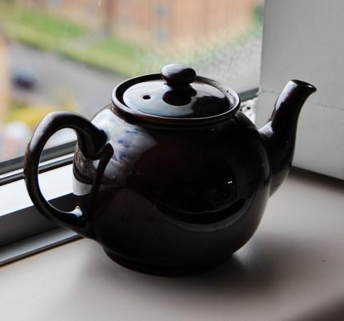 A black teapot on a windowsill