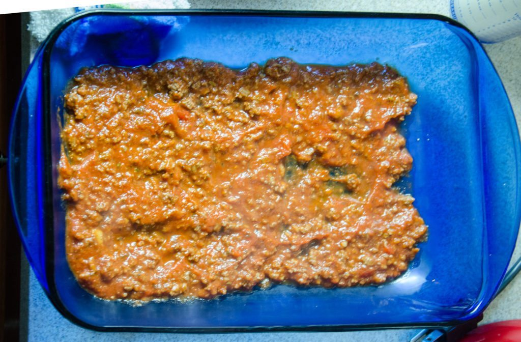 Cover bottom of pan with thin layer of meat mixture (meats, spaghetti sauce, spices).