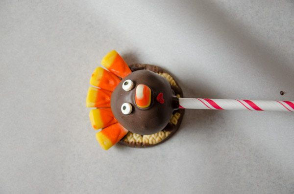 While chocolate is still wet, place candy corn on for nose. Use heart-shaped sprinkle, upside down, for mouth. Add candy eyes. If chocolate hardens too much, use a small amount of wet chocolate on the back of mouth/eyes to get it to stick.