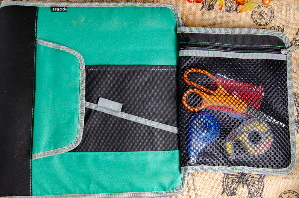 Use a zipper binder. The front flap is useful for storing scissors, tape, calculator, or store cards.