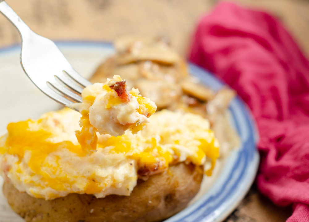 Close-up of Entire dish of Twice-Baked Potatoes. Potatoes mixed with cheese, butter, sour cream, cream cheese, and bacon. Creamy, cheesy, delicious side dish that can be made in advance! #potatoes #twicebakedpotatoes #sidedish #bacon #cheese