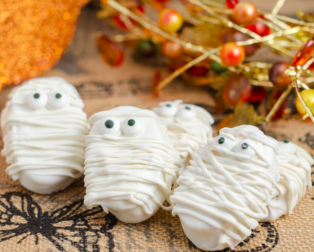 Halloween Mummies. White chocolate, peanut butter filling, decorated for Halloween. No-bake dessert that is cute and so delicious! #halloween #halloweenmummies #mummies #peanutbutter #whitechocolate