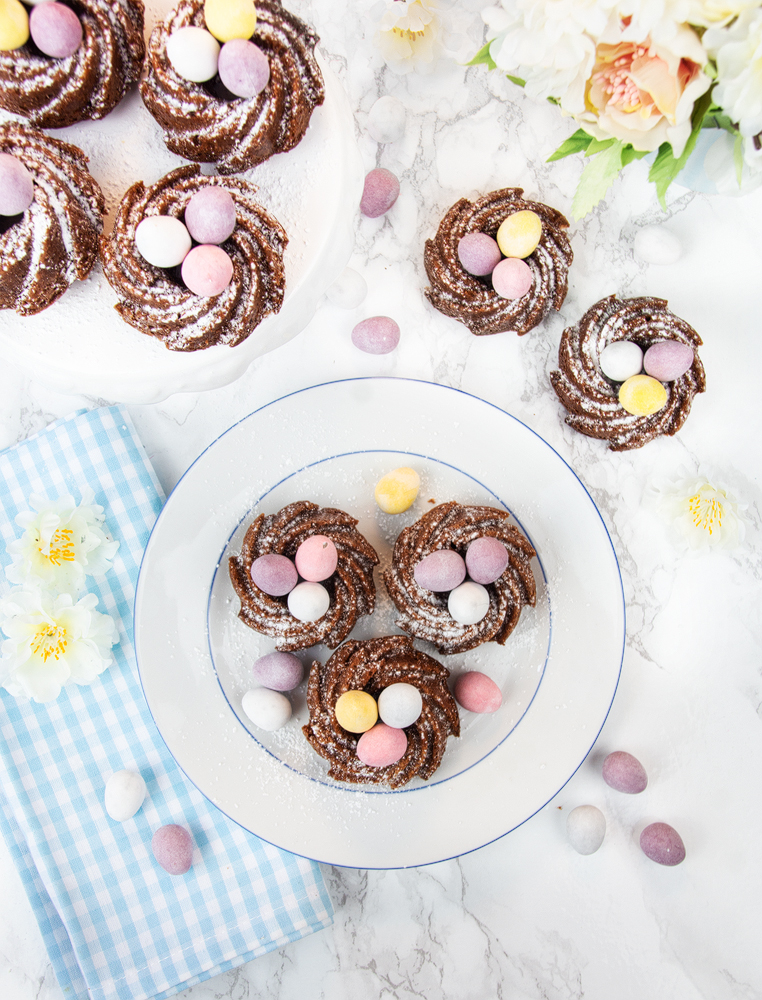This mini chocolate bundt cake recipe is perfect for Easter. Made with a delicious chocolate batter and decorated with mini chocolate eggs. #bundt #minibundt #cake #Easter