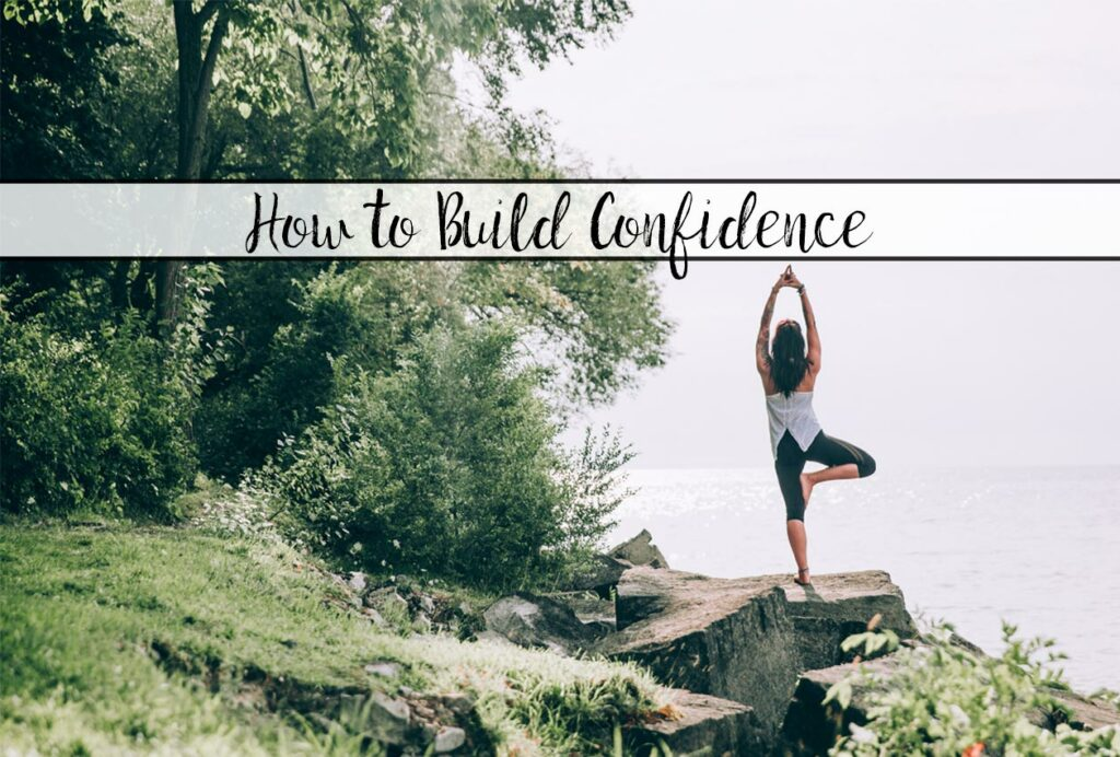 Featured image for article on how to build confidence. Woman in yoga post next to water.