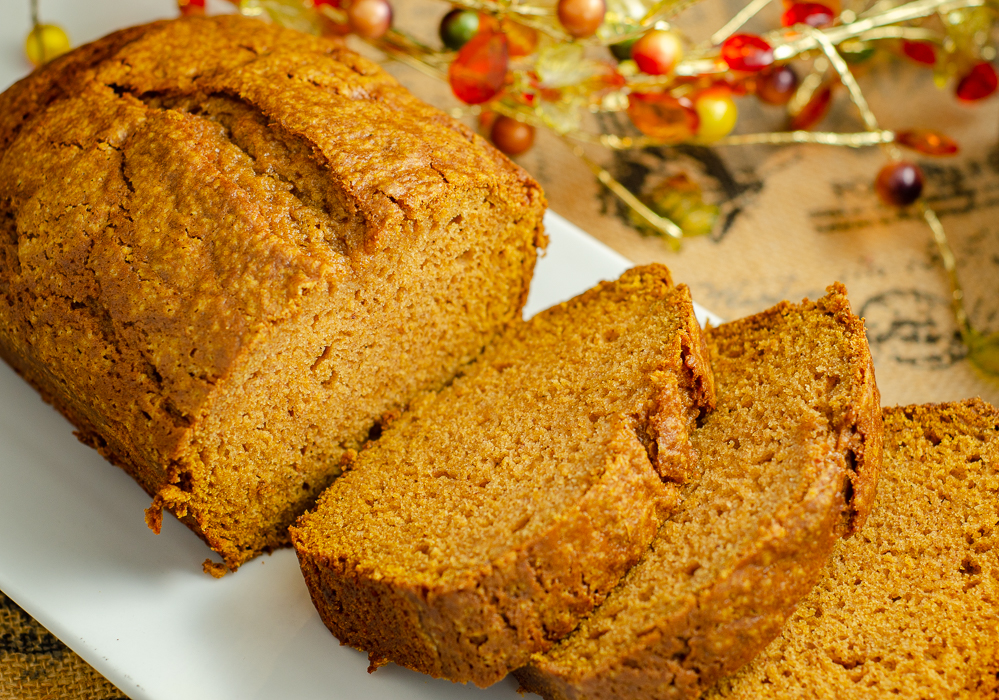 Loaf of pumpkin bread with three slices spread out.