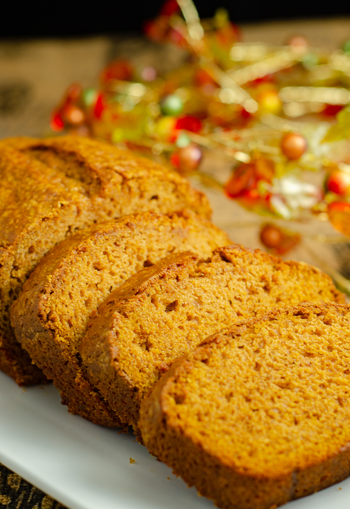 Vertical image: Loaf of pumpkin bread with three slices spread out.