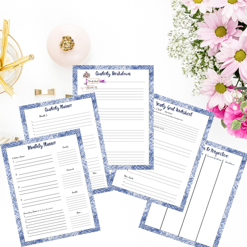 Goal worksheets in personal money management. Spread out with flowers and gold pens.