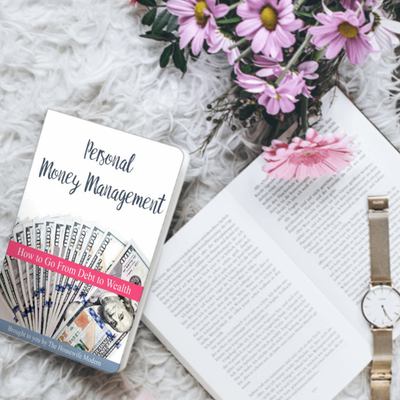Image of personal money management book with flowers, book, and watch.