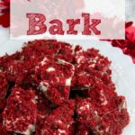 Pin image for red velvet bark. Close-up of bark piled on white plate with red tinsel in background with text overlay.