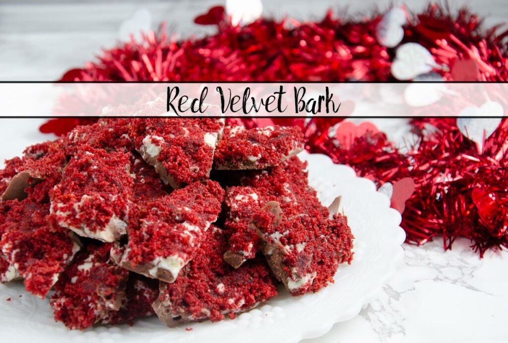 Featured image for red velvet bark. Close-up of bark piled on white plate with red tinsel in background.