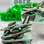 Pin image for mint oreo bark. Stack of mint oreo bark in foreground. White bowl full of mint oreo bark with green tinsel in background.