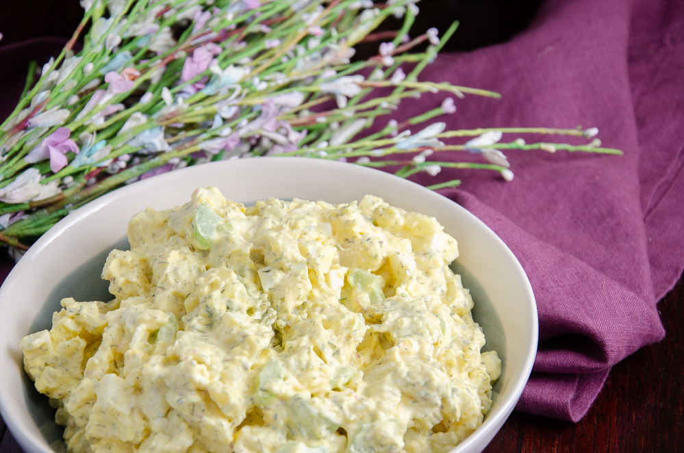 Featured image best classic potato salad. White bowl on purple napkin.