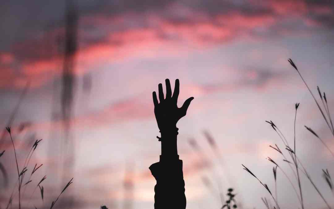 Shadow of hand raised in front of sunset