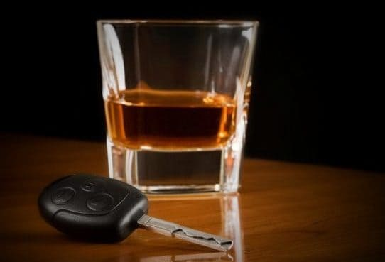 Glass of whiskey with a set of keys next to it symbolizing your ability to hire a qualified Houston DWI Lawyer