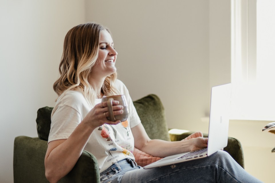 Woman smiling while checking emails and holding a coffee cup.