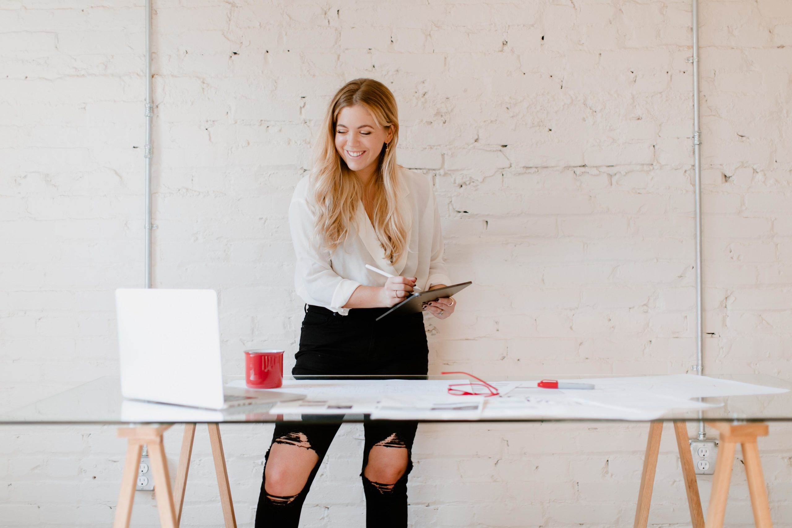 Woman is standing behind messy desk, smiling and taking notes on a paper.