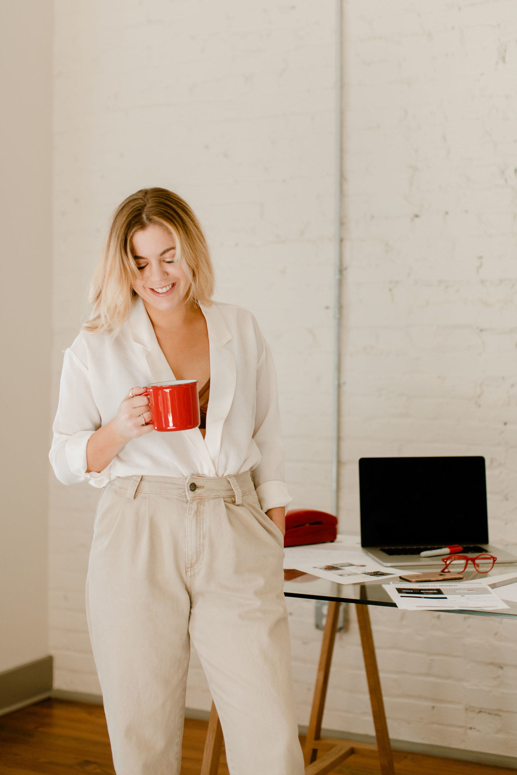 This is a portrait of a woman holding a red coffee mug with a messy desk in the background.