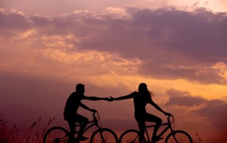 Man and woman holding hands on bicycle