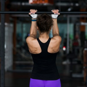 woman wearing gloves doing pull ups