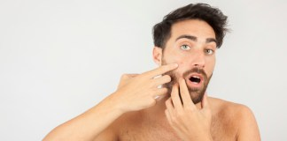 man pointing at pimple on his face