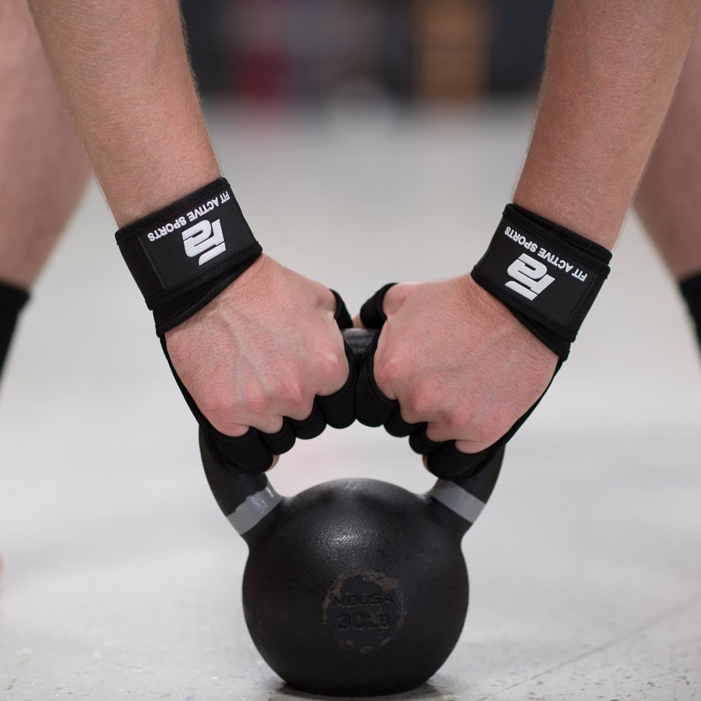 Fit man lifting kettlebell wearing weight lifting gloves black