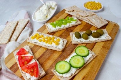 homemade-crispbread-toast-with-cottage-cheese-green-olives-slices-cabbage-tomatoes-corn-green-pepper-cutting-board-healthy-snacks