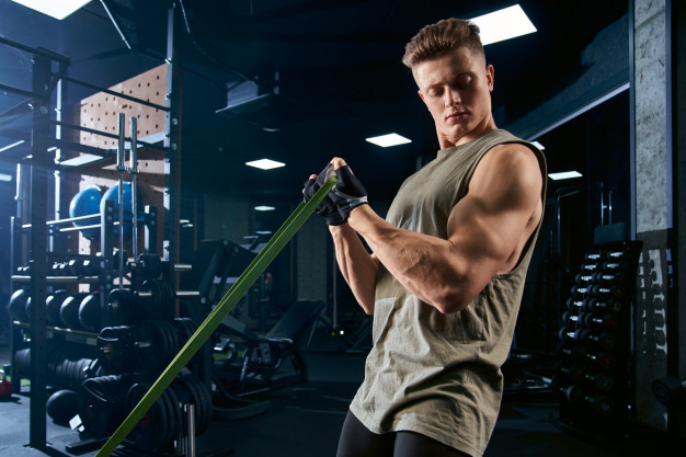 fit guy working out arms resistance band