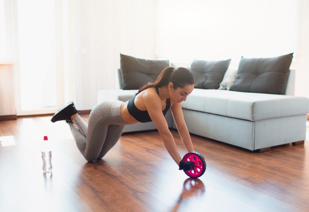 fitgirl doing abs exercise ab wheel