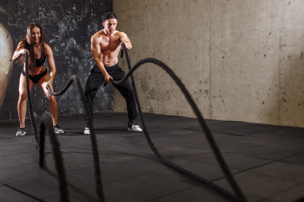 woman-man-couple-training-together-doing-battling-rope-workout_HIIT