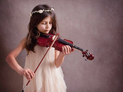 girl wearing a tulle dress learning to play violin