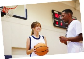 Young female basketball player talking to her coach