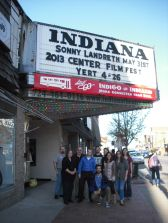 "Center organizing members, ""YERT"" producer Mark Dixon, musician Scott Ellis, and a representative of the Indiana Municipal Waste Authority standing beneath the sign of the Indiana Theater."