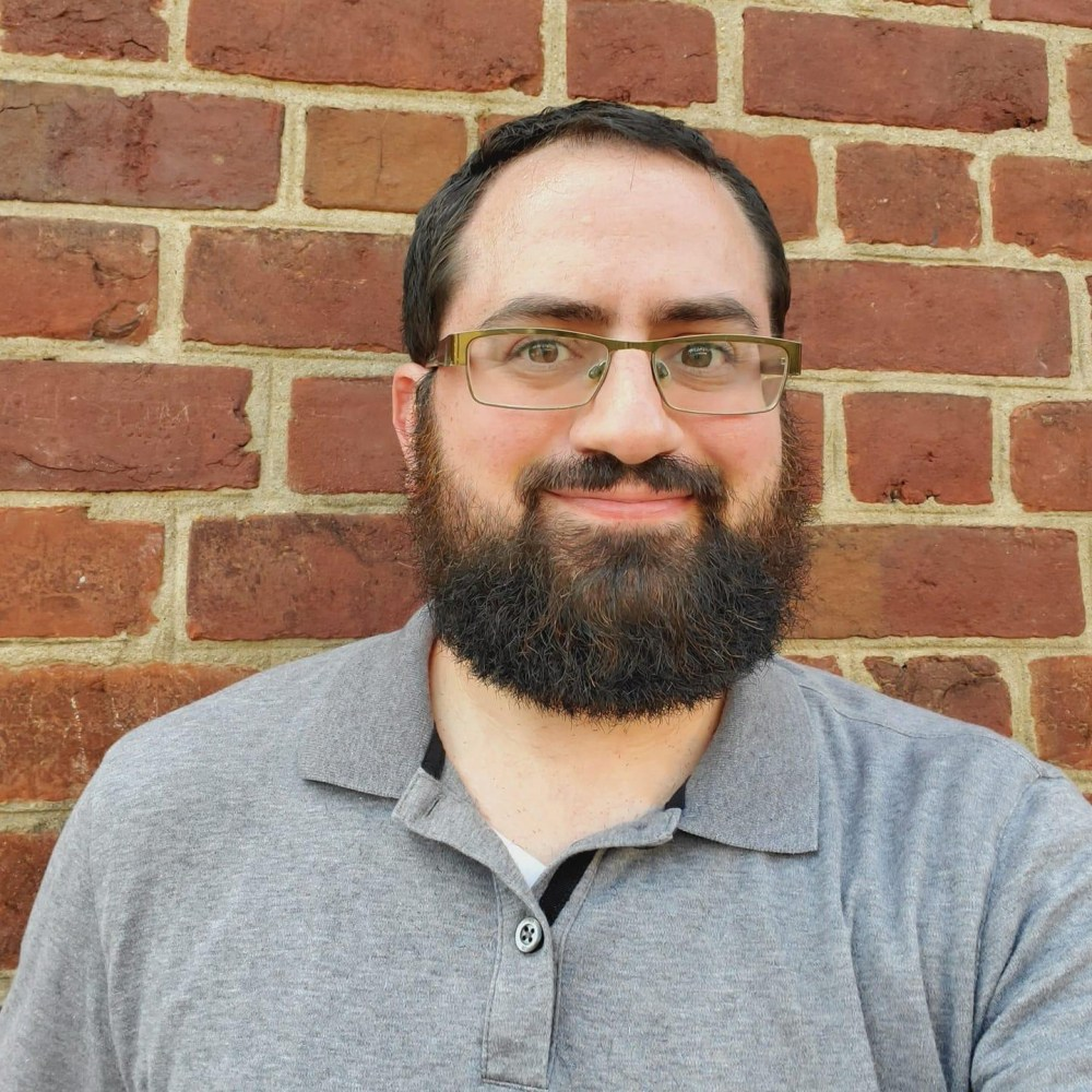 Head and shoulders photo of the writer Phil Goldstein standing in front of a brick wall.