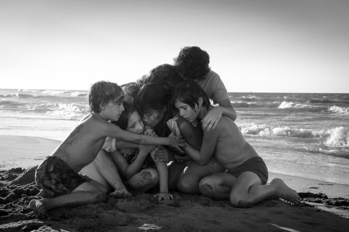a family hugging each other on a beach