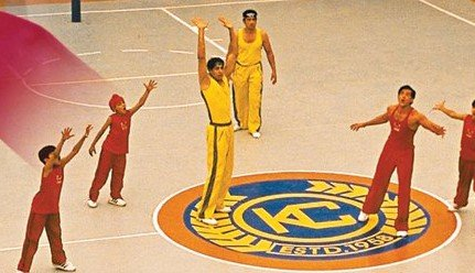 a basketball court with players from two different teams signified by red and yellow jersey