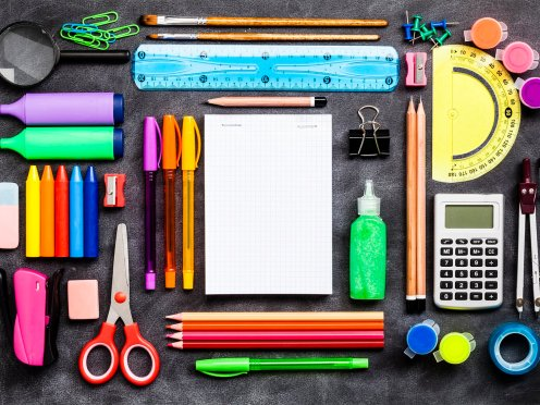 office supplies shot on rustic black background. A blank note pad is at the center and othe stationary items at the side