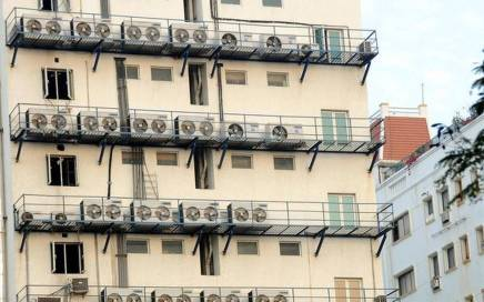 the outside view of a building with many of a/c outlets shown in the balcony