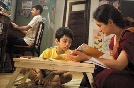 a kid sittiking with his mother and looking in a notebook