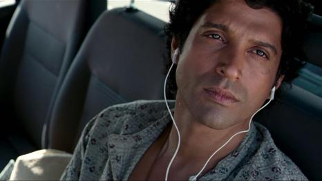 a man looking outside the window of a car listening to music on earphones