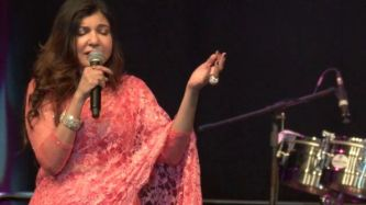a woman wearing a saree singing on the stage with one hand up high and other holding the mic