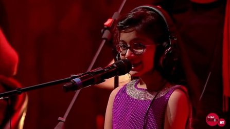 a little girl singing on the mic wearing headphones and red stage light shining at the back