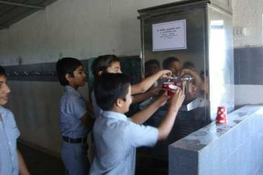 few children filling water from the watercooler in school