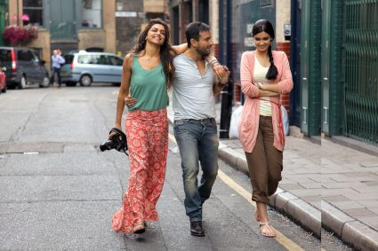 a couple walking together hands locked on shoulders and another girl walking with them