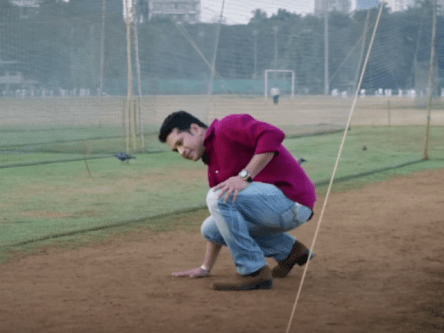 a man touching and checking the dampness of a cricket field