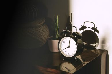 an alarm clock kept on a bedside table, showing the perks of living alone